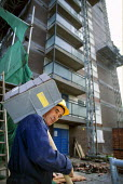 Construction worker carrying a hod of bricks on site of refurbished tower block, Manchester - Paul Herrmann - bricklayers,2000s,2002,block,blocks,brick,bricklayer,BRICKLAYERS,bricklaying,bricks,builder,builders,building,building site,BUILDINGS,burden,carries,carry,carrying,cities,city,Construction industry,EB