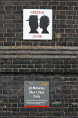 Warrington Bank Quay railway station, UK, has introduced a kissing zone, and a no kissing zone, the latter to avoid obstructions at the taxi rank. - Paul Herrmann - 2000s,2009,affection,affectionate,Bank,BANKS,Brick Wall,communicating,communication,delay,delays,drop-off,journey,journeys,kiss,kissing,ncp,network,PARKED,parking,passenger,passengers,people,point,RAI