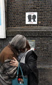 Warrington Bank Quay railway station, UK, has introduced a kissing zone, and a no kissing zone, the latter to avoid obstructions at the taxi rank. Here, two relatives kiss goodbye before a journey. - Paul Herrmann - 2000s,2009,affection,affectionate,Bank,BANKS,Brick Wall,communicating,communication,delay,delays,drop-off,embrace,EMBRACING,goodbye,good-bye,hug,hugs,journey,journeys,kiss,kissing,NCP,passenger,passen