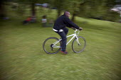 A young man cycles through a park in Manchester, UK, at dusk. - Paul Herrmann - 06-06-2009