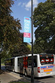A bendy park & ride bus passes a sign for York Car Free Day 22nd September 2009, on a road into York. - Paul Herrmann - ,2000s,2009,adult,adults,AUTO,AUTOMOBILE,AUTOMOBILES,AUTOMOTIVE,bus,bus service,BUSES,car,cars,cities,city,communicating,communication,COMMUTE,commuter,commuters,commuting,emissions,ENI environmental