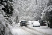 A four-wheel drive car drives along a wintry suburban road Manchester, UK - Paul Herrmann - 2010,2010s,4x4,AUTO,AUTOMOBILE,AUTOMOBILES,AUTOMOTIVE,car,CARS,cities,city,DRIVER,DRIVERS,driving,highway,ice,icy,Manchester,precipitation,road,roads,season,seasonal,Severe Weather,snow,snowfall,snowi