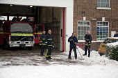 Firefighters clear snow from the front of a fire station Withington, Manchester, UK - Paul Herrmann - 05-01-2010