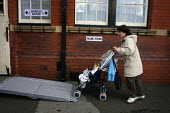 A mother and baby in a pushchair enter a polling station in Stockport, Greater Manchester, using the disabled access ramp at the 2001 general election - Paul Herrmann - 2000s,2001,access,babies,Baby,bound,buggy,child,CHILDHOOD,children,democracy,disabilities,DISABILITY,disable,disabled,disablement,EARLY YEARS,election,elections,families,family,female,incapacity,infan