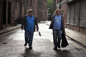 Two young men in a street in the Northern quarter of Manchester help clean up after the riots of the previous night - Paul Herrmann - 10-08-2011