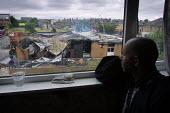 A local Asian resident overlooking the smoking remains of Manningham Labour Club the morning after riots in Bradford - Paul Herrmann - 08-07-2001