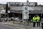 Police guard the burnt-out remains of Lister Park BMW car showroom in Manningham, the morning after riots in Bradford - Paul Herrmann - 08-07-2001
