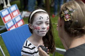 A girl has her face painted to read Save A+E, at a march and rally, Urmston, Manchester, to protest at the threatened cuts including closure of the Accident and Emergency department at Trafford Genera... - Paul Herrmann - 07-07-2012