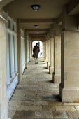 A man walking down a covered alley in Poundbury, the Prince of Wales's model village on the outskirts of Dorchester, UK - Paul Herrmann - 2000s,2002,ACE,architecture,arts,buildings,Charles,communities,community,culture,development,Dorset,good,houses,housing,model,models,pastiche,people,positive,Poundbury,prince,retro,soi social issues,t