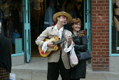 A street performer serenades a shopper in Wigan, UK - Paul Herrmann - 2000s,2002,ACE culture & entertainment,amuse,amusement,ann,boater,bought,busk,busker,buskers,busking,buy,buyer,buyers,buying,commodities,commodity,consumer,consumers,crooner,crooning,customer,customer