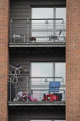 The balconies of two flats in Manchester, UK, with toys and furniture piled up - Paul Herrmann - 2010,2010s,apartment,apartments,balcony,brick,BRICKS,cramped,EBF,Economic,Economy,flat,flats,home,homes,housing,LFL lifestyle & leisure,lifestyle,Manchester,modern,space,steel,terrace,Terraced,Terrace
