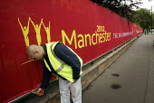 A workman puts the finishing touches to security fencing round the athletes' village in preparation for the Commonwealth Games in Manchester UK - Paul Herrmann - 09-07-2002