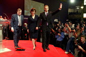 Prime minister Tony Blair acknowledges applause with his wife Cherie Booth and deputy John Prescott after his speech at Labour Party Annual Conference 2002, Blackpool, UK - Paul Herrmann - 2000s,2002,applauding,applause,Cheri,Conference,conferences,leader,minister,ovation,Party,photographers,PM,POL politics,press,speech,stage,wave,waving