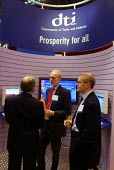 Businessmen talking at the DTI stand at the CBI conference in Manchester; sign reads Prosperity for all. - Paul Herrmann - 25-11-2002