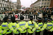 Police link arms to stop an anti-war protest in Manchester on the first day of war against Iraq. Banners read Natfhe, Demonstrate - Paul Herrmann - 2000s,2003,activist,activists,adult,adults,against,anti war,Antiwar,asian,BAME,BAMEs,BANNER,Banners,barrier,black,BME,bmes,CAMPAIGN,campaigner,campaigners,CAMPAIGNING,CAMPAIGNS,cheer,CLJ,coalition,DEM