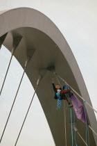 Anti-war protestor wearing a Tony Blair mask hangs a banner from Hulme Arch bridge in Manchester. Banner reads No War - Paul Herrmann - 26-03-2003