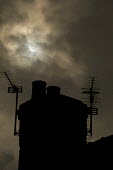 Partial solar eclipse over house roof, as the moon moves infront of the sun, Manchester, UK - Paul Herrmann - 2010s,2015,aerial,aerials,chimney,chimneys,cloud,clouds,eni,environment,Environmental Issues,house,houses,Manchester,moon,nature,roof,roofs,rooftop,rooftops,sun,THE ATMOSPHERE,WEA weather,weather
