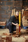 Female student at Mancat college, Manchester, learns building and bricklaying skills - Paul Herrmann - 2000s,2004,adolescence,adolescent,adolescents,apprentice,Apprentices,apprenticeship,BRICK,bricklayer,bricklayers,bricklaying,bricks,builder,builders,by hand,college,COLLEGES,Construction Industry,EDU