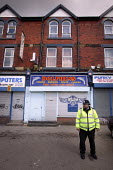 A policeman outside the flat in Manchester at which arrests were made under the terrorism act. - Paul Herrmann - 2000s,2004,adult,adults,arrested,burgers,CLJ crime law & justice,crime scene,dolphin,fast food,fast food,fastfood,flat,force,house,houses,kebab,kebabs,Manchester,OFFICER,OFFICERS,outlet,outlets,outsid