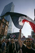 """Protestor waves flag at the """"Time to go"""" anti-war march in Manchester on the eve of Labour Party Conference - Paul Herrmann - 23-09-2006"""
