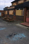 Broken glass and boarded-up windows at the Live and Let Live pub in Glodwick, Oldham, Lancashire after it had been attacked by rioters - Paul Herrmann - 28-05-2001