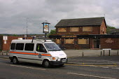 Police van drives past the Live and Let Live pub in Glodwick, Oldham, Lancashire after it had been attacked by rioters - Paul Herrmann - 28-05-2001