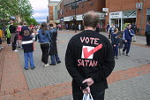 A man shopping in Oldham, Lancashire wearing a shirt carrying the slogan Vote Satan. The slogan is that of the musician Marilyn Manson. - Paul Herrmann - ,2000s,2001,ACE culture,anti-christian,apathy,ballot,BALLOTING,ballots,bought,buy,buyer,buyers,buying,campaign,campaigning,CAMPAIGNS,carries,carry,carrying,commodities,commodity,consumer,consumers,cus