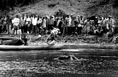 Rwandan refugees wait to cross into Tanzania as a victim of the genocide goes floating past in the river on the Rwanda - Tanzania border. 1994. - Howard Davies - 1990s,1994,africa,BAME,BAMEs,BME,bmes,bodies,body,border,borders,conflict,conflicts,cross,crosses,crossing,dead,dead body,death,deaths,Diaspora,died,displaced,diversity,EQUALITY,ethnic,Ethnic Cleansin