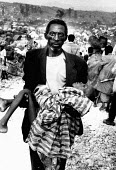 Rwandan refugee carrying his sick child to MSF cholera hospital, Kitale camp, Goma, Zaire-Congo. 1994 - Howard Davies - 03-05-1994