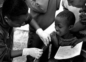 A Rwandan refugee child having measles vaccination at a Red Cross camp, Bukavu, Zaire-Congo. 1994 - Howard Davies - 03-05-1994