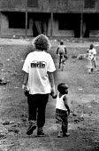 Aid worker from MERLIN with repatriated Rwandan refugees waiting to go home from border transit camp, Gisenyi, Rwanda. 1996. - Howard Davies - 03-05-1996