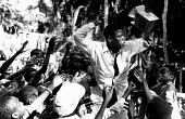 Local aid worker gives food to Rwandan Hutu refugees at Biaro camp in aftermath of massacre by rebels. Zaire-Congo. 1997 - Howard Davies - 05-08-1997