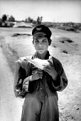 Afghan refugee boy carrying a dove on his way back to his camp. Hawaii refugee camp. NWFP, Pakistan. 1989 - Howard Davies - 1980s,1989,Afghan,afghanistan,afghans,asia,asian,asians,camp,camps,carries,carry,carrying,child,CHILDHOOD,children,Diaspora,displaced,foreign,foreigner,foreigners,immigrant,IMMIGRANTS,immigration,indi