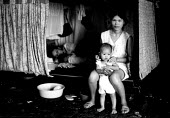 Vietnamese refugee family in closed detention center. Sham Shui Po detention centre, Hong Kong. 1988 - Howard Davies - 1980s,1988,adult,adults,asia,boat,BOATS,camp,camps,CHILD,CHILDHOOD,children,china,closed,closing,closure,closures,detention,Diaspora,displaced,families,family,FEMALE,foreign,foreigner,foreigners,Hong