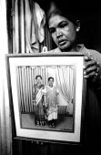 A mother holds a photograph of her two daughters who were both lost in the Tsunami, and lives in an IDP camp, Batticaloa, Sri Lanka 2005 - Howard Davies - 11-08-2005