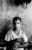 A Tamil child whose family have been displaced by the conflict in northern Sri Lanka and have found refuge in the Jaffna train station, which has been largely destroyed in the conflict. Jaffna, Sri La... - Howard Davies - 11-08-2005