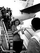 Kosovar Albanian refugees arriving on evacuation flight, Manchester airport, UK, 1999 - Howard Davies - 1990s,1999,adult,adults,air transport,airline,airport,AIRPORTS,Albanian,Albanians,ARRIVAL,arrivals,arrive,arrived,arrives,arriving,BALKAN,balkans,Balkans Conflict,BAME,BAMEs,Black,BME,bmes,britain,CHI
