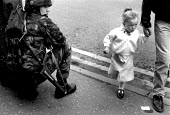 Child passing a British soldier on the street with plastic bullet gun, Belfast, Northern Ireland, 1989 - Howard Davies - ,1980s,1989,armed,Armed Forces,arms,army,Baton Round,baton rounds,britain,Bullets,child,CHILDHOOD,children,cities,city,conflict,conflicts,female,females,girl,girls,gun,guns,Ireland,Irish,juvenile,juve