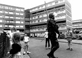 British soldier on patrol while children play, West Belfast, Northern Ireland, 1989 - Howard Davies - ,1980s,1989,armed,Armed Forces,arms,army,britain,child,CHILDHOOD,children,cities,city,conflict,conflicts,female,females,girl,girls,Gun,guns,Ireland,Irish,juvenile,juveniles,kid,kids,male,man,men,milit