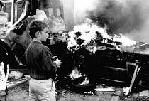 Children at burning barricade, West Belfast, Northern Ireland, 1989 - Howard Davies - 01-08-1989
