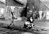 Children throwing stones at the army, West Belfast, Northen Ireland, 1989 - Howard Davies - 1980s,1989,activist,activists,adolescence,adolescent,adolescents,against,armed forces,army,britain,CAMPAIGN,campaigner,campaigners,CAMPAIGNING,CAMPAIGNS,CHILD,CHILDHOOD,children,cities,city,conflict,c