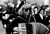 Republican protest with IRA on accordion. West Belfast, Northern Ireland. 1989 - Howard Davies - ,1980s,1989,activist,activists,Arts,britain,CAMPAIGN,campaigner,campaigners,CAMPAIGNING,CAMPAIGNS,cities,city,conflict,Conflict ACE,conflicts,culture,DEMONSTRATING,demonstration,demonstrations,FEMALE,