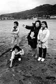 Teacher with refugee children from Vietnam and Cambodia at reception centre, Barmouth, Wales. UK. 1989 - Howard Davies - 1980s,1989,agencies,agency,aid,assistance,BAME,BAMEs,beach,BEACHES,Black,BME,bmes,britain,charitable,charities,charity,CHILD,CHILDHOOD,children,COAST,coastal,coasts,Diaspora,displaced,diversity,edu,ed