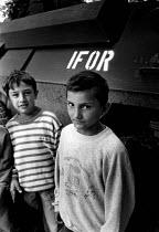 Bosnian Muslim children recently returned home having been refugees stand by a NATO IFOR tank on patrol in postwar Kljuc, Bosnia 1996 - Howard Davies - 01-07-1996