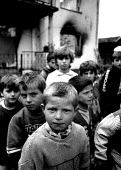 Kosovar Albanian children in a village where Serb forces massacred forty five men from their families. Trjne, Prizren, Kosovo 1999 - Howard Davies - 1990s,1999,Albanian,Albanians,Balkan,balkans,BAME,BAMEs,BME,bmes,CHILD,CHILDHOOD,children,conflict,conflicts,diversity,ethnic,Ethnic Cleansing,ethnicity,europe,housing,juvenile,juveniles,kid,kids,koso