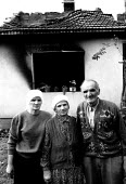 Kosovar Albanian family outside their house in a village where Serb forces massacred their son, one of forty five men from the village. Trjne, Prizren, Kosovo 1999 - Howard Davies - 1990s,1999,age,ageing population,Albanian,Albanians,Balkan,balkans,BAME,BAMEs,BME,bmes,conflict,conflicts,diversity,elderly,ethnic,Ethnic Cleansing,ethnicity,europe,families,family,FEMALE,house,houses