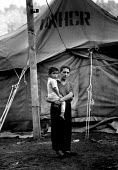 Roma family outside their UNHCR tent in an IDP camp where they are protected by NATO KFOR troops from reprisal attacks by Kosovar Albanians, who alleged they colloborated during the war. Obilic IDP ca... - Howard Davies - 01-07-1999