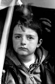 A Kosovar Albanian refugee boy waits to be moved from a transit border camp at Blace having been forced from their homes by Serb forces. Macedonia - Kosovo border. 1999 - Howard Davies - 1990s,1999,Albanian,Albanians,balkan,balkans,border,border control,border controls,borders,camp,camps,CHILD,child children,CHILDHOOD,children,conflict,Diaspora,displaced,eu,europe,european,europeans,e