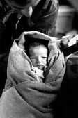 A newly born baby with their Kosovar Albanian refugee family in an Israeli medical tent in the Brazde camp established by NATO. Macedonia. 1999 - Howard Davies - 01-07-1999