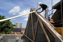 Housing construction workers - Paul Herrmann - 2000s,2002,beam,beams,breeze block,breeze blocks,bricklayer,bricklayers,bricklaying,builder,builders,building,building site,BUILDINGS,cities,city,Construction Industry,EBF economy,hard hat,hat,hats,he